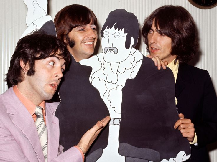Paul McCartney, Ringo Starr and George Harrison pose with a cartoon cut-out of fellow Beatle John Lennon at a press review of the group's animated film 'Yellow Submarine'.  photo by Bill Zygmant