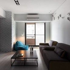 二つのソファーが置かれた広いリビングルーム。柱はブリック柄の壁紙にしました。壁には魚が勢いよく泳ぐオブジェが。ビーズクッションをデイベッド代わりに、窓際に置きました。