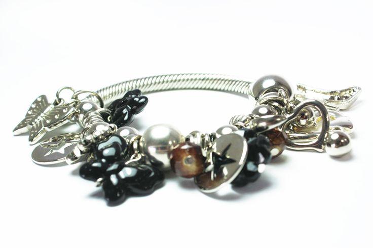 De dijes grandes y cadenas color en plata, Desenlaces es la pulsera que más va con tus blusas de manga 3/4. ¡Recomendada!