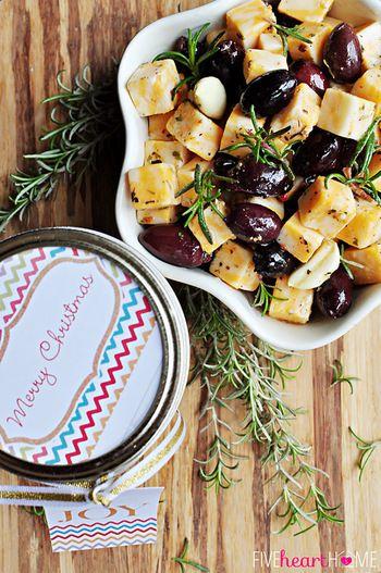 【チーズとオリーブのマリネ】 材料(約6瓶分程度):コルビージャックチーズ約230g(もちろん他のチーズでもOK。マイルドテイストがマリネとマッチしておすすめ)、ブラックオリーブ1瓶/約340g(水気をよく切る)、オイル&ビネガーもしくはイタリアンサラダドレッシング1瓶/約450g、イタリアンシーズニング大さじ1、カイエンペッパー小さじ1/2、にんにく6かけ(潰す)、ローズマリー(生)6茎  作り方:①大きめのボールにローズマリー以外の材料をすべて入れ、優しく混ぜ合わせます。②ラップや蓋でカバーして冷蔵庫で最低8時間~24時間冷やし漬けます。③②の具材を6つのガラス瓶(メイソンジャーのようなもの)に分け、ローズマリーを一茎ずつ各瓶にのせ、残っている漬け汁を均一に注ぎ分けます。冷蔵庫で2週間まで保存可能です。