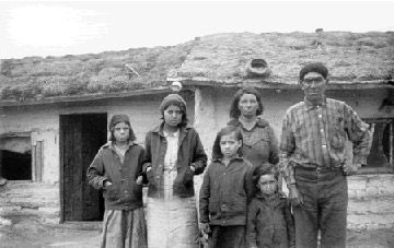 Métis family in front of home