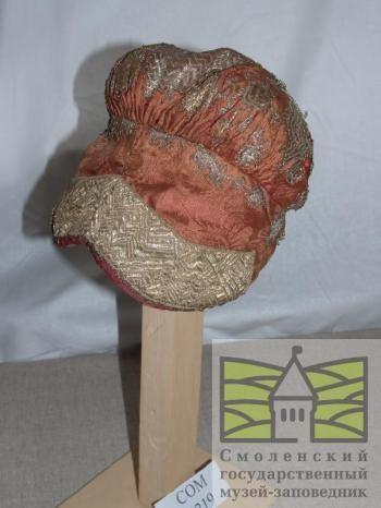 Музейное описание: Повойник. Мягкий красный камки, верхняя часть зашита золотным и серебристым рисунком, на козырьке золотной галстук. Затыльная часть в бантовых складках, подкладка пестрого ситца.