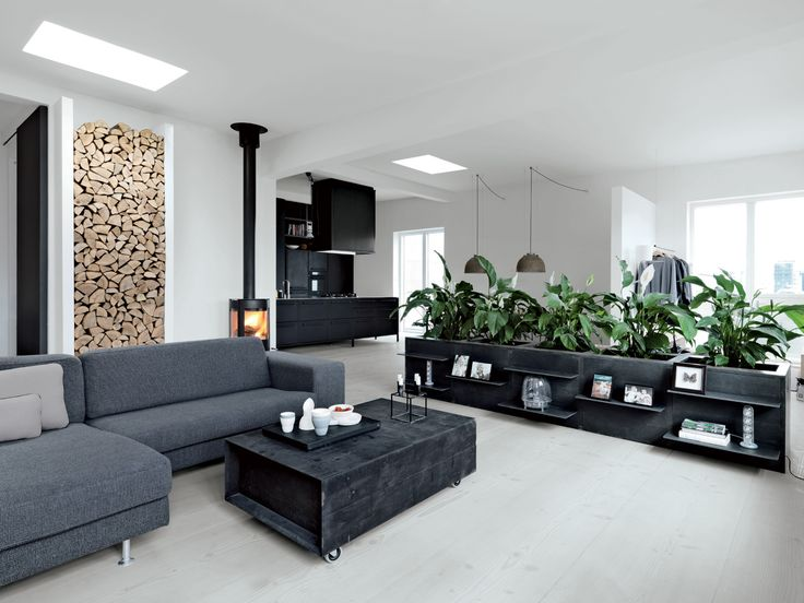 """The living features a sofa from Engell; a suspended Parentesi lamp by Achille Castiglioni and Pio Manzù for Flos (Olsen's """"all-time favorite.""""); and a wood-burning stove made by Aduro. The firewood nook set in the left wall is Jensen's own design. Olsen is responsible for the low planters around the perimeter, which she had fabricated from poured concrete framed in welded iron, with lacquered MDF panels for doors. """"Some people laughed because we;d never had plants in our apartment,"""" she…"""