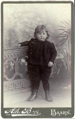 Adriaan Boer   Portretten. Studioportretten Nederland. Studiofoto van een peuter in donkere kleding en halfhoge rijglaarsjes. Hij heeft zijn hand op de balustrade gelegd. Baarn, tussen 1897 en 1912.
