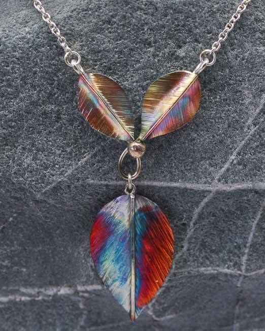 Fold formed, sawn and hammered copper leaf necklace pendant with heat patina.  The leaves are approx 30mm x 18mm and 20mm x 12mm joined with silver wire.  Overall length of 41mm with a drop of 60mm.  Sterling silver chain.  #copper #leaf #necklace #pendant #silver #jewellery #cornwall #uk #gb #westcountry #devon #england #silversmith #pretty #jeweller #jewellers #handmadejewellery #handmade