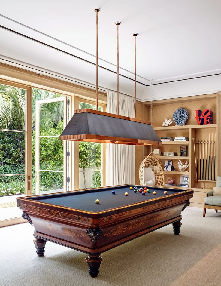 """Anchoring the game room is a spectacular antique billiard table and a Tessier-designed copper-and-bronze chandelier. """"I found the table by pure luck through a French pool table maker who happened to have it in his workshop,"""" says Tessier. """"It's antique, circa 1830."""""""