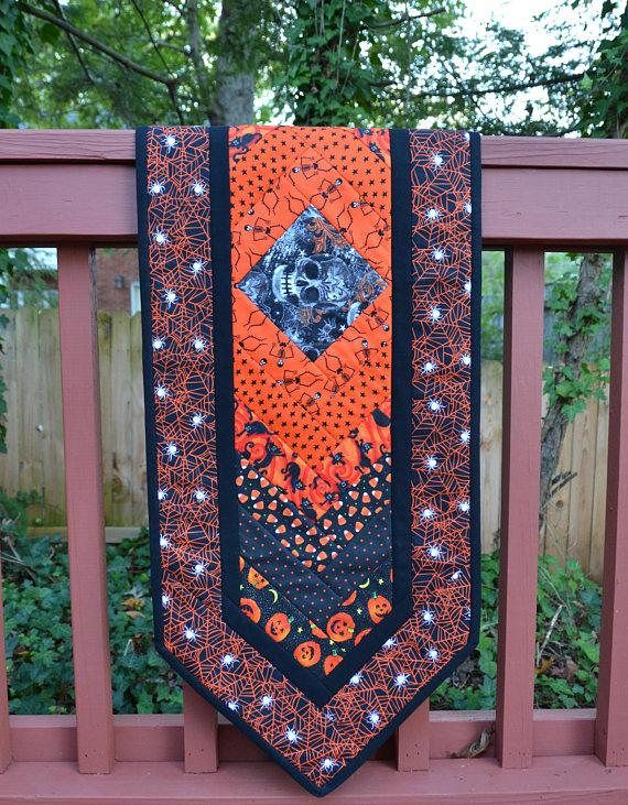 Skull Table Runner/Wall Hanging  Enter Coupon Code THENEWYEAR for 10% discount at checkout through January 31, 2018  The orange spider web fabric featuring white spiders against the black fabric strips creates a dramatic effect as the border on this skeleton quilt.   https://www.etsy.com/listing/551761886/skull-table-runner-skull-quilt-halloween  #skull #quilt #pumpkin #table #runner #halloween #tablecloth #cat #spider #witch #black #orange #decor #gray #stars #web