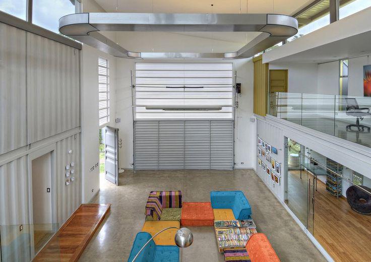 Diseño de sala a doble altura de casa construida con contenedor
