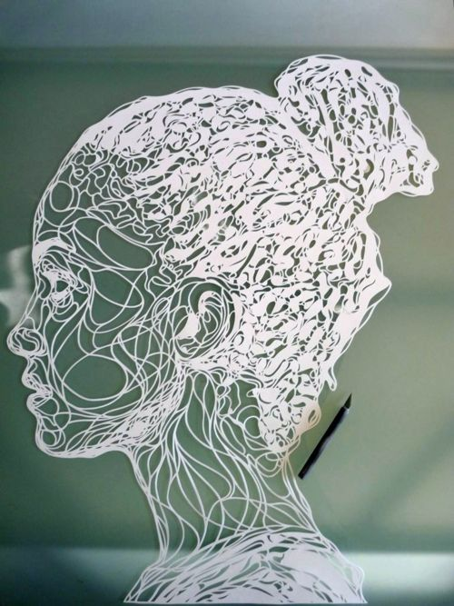 Kris Trappeniers cuts paper portraits to use as stencils