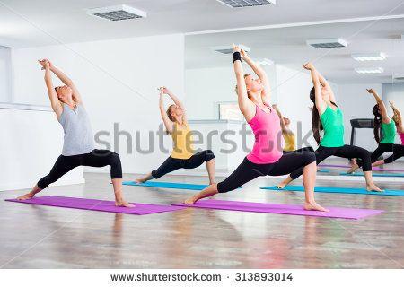 Four girls practicing yoga, Yoga - Virabhadrasana/Warrior pose - stock photo