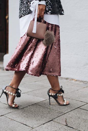 Nina Schwichtenberg trägt einen schwarzen Pailletten Blazer, einen rosa Rock ebenfalls mit Pailletten, dazu eine weiße lange Bluse, Perlensandalen von Paula Cardemartori & als Accessoire die Aigner Mini Bag mit Puschel. Mehr auf www.fashiioncarpet.com