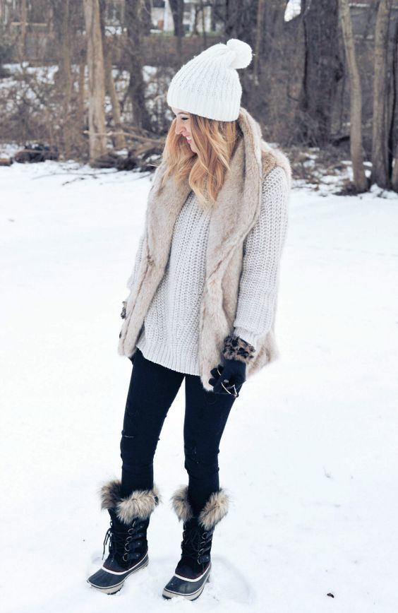 Wear a beige fur vest with black slim jeans for a refined yet off-duty ensemble. Black snow boots will give your look an on-trend feel.   Shop this look on Lookastic: https://lookastic.com/women/looks/vest-oversized-sweater-skinny-jeans/23478   — White Beanie  — Beige Fur Vest  — White Knit Oversized Sweater  — Black Skinny Jeans  — Black Snow Boots