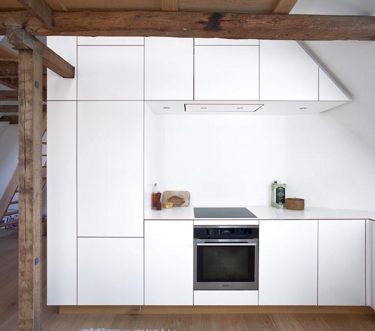 The heavy wooden beams contrasts the minimalistic white laminate in this oak kitchen by NicolajBo // Snedkerkøkken, Vesterbro, København