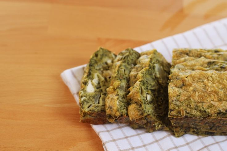 Spinazie-cake. Ingrediënten: • 450 gram (1 doosje) fijn gehakte spinazie • 2 grote uien • 5 eieren • 150 ml (plantaardige)melk • 180 gram tarwebloem / roggebloem / spelt / ander soort meel of bloem • 150 gram geitenkaas • 100 gram geraspte kaas (optioneel) • olijfolie om in te bakken • peper, zout en basilicum