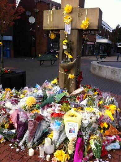 Impromptu memorial to the beheaded Salford cab driver Alan Henning at the Cross in Eccles, Manchester, England, United Kingdom, 2014, photograph by Edwina Wolstencroft. Henning was killed after years working as a volunteer with Syrian refugees, wherein much of his time and own money was donated to help benefit those displaced by war in the region, money earned through his job as a cab driver. In the days following his death a fund set up for his 2 children had already raised over £17,000.