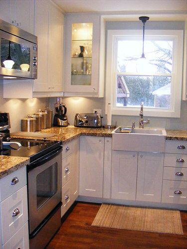 Ikea Akurum white cabinets, tiny space,  farmhouse sink. Change the counter to butcher block & appliances to white & this is my kitchen!