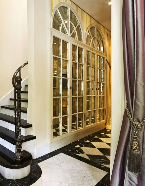 Old french doors were mirrored & hung to make a narrow hallway look bigger.