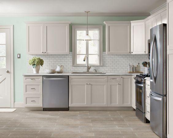 Kitchen facelift: Refacing old cabinets...subway tile backsplash.. Ceramic wood grain tile floor... White painted cabinets.. Mint walls: