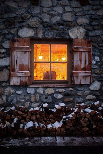 A chill in the air. A bit of snow. A wood pile. And a cozy light in the window. It's Fall.