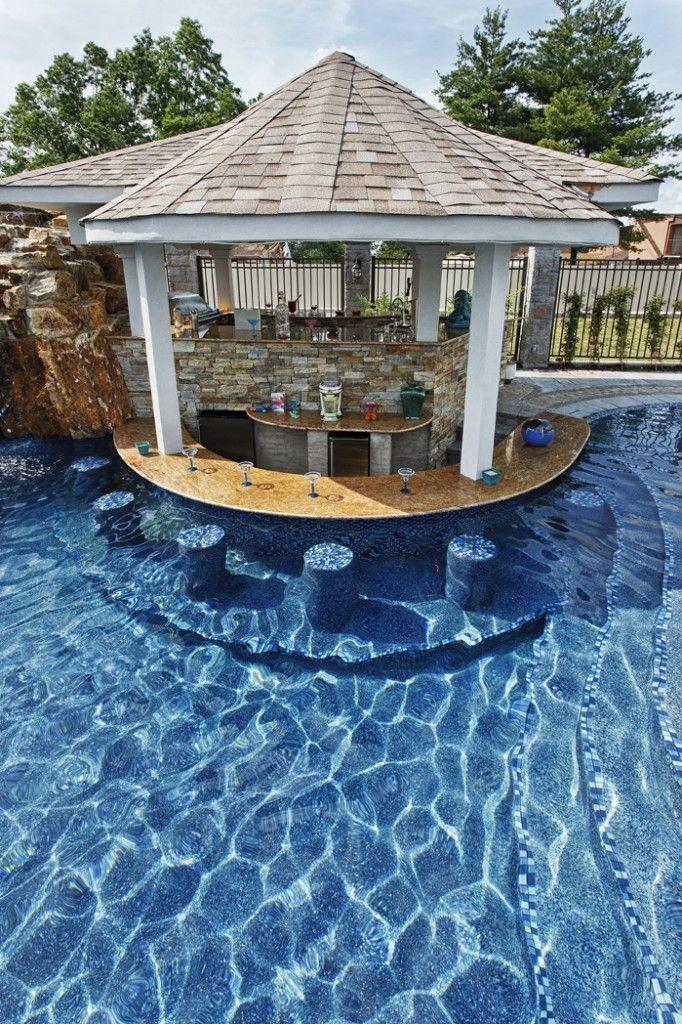 La cocina de fuera con la piscina. Los taburetes y la mesa son en el agua. Personas pueden nadar mientras comer.
