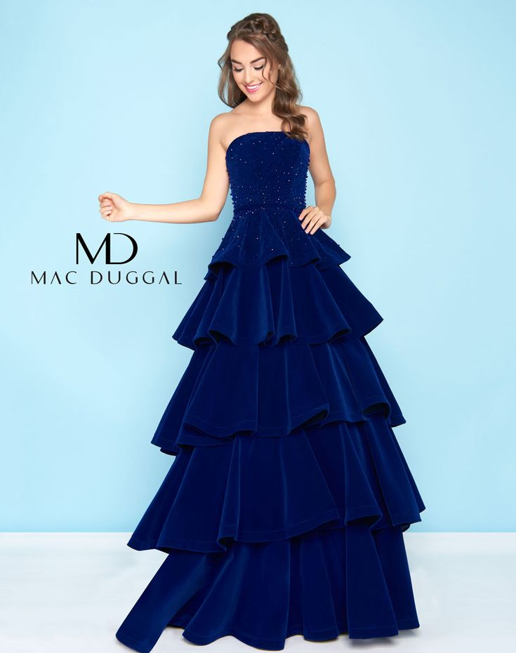 Be on trend in the full velvet ballgown! The strapless gown embellished with english cut beading gives way to full tiered ruffle velvet skirt.