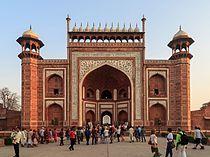 Darwaza de acesso ao Taj Mahal – As paredes e os tectos abobadado apresentam elaborados desenhos geométricos, similares aos que existem em outros edifícios do complexo. Originalmente a entrada fechava-se com duas grandes portas de prata, que foram desmontadas e fundidas pelos jats em 1764.   O masjid, a mesquita No extremo do complexo erguem-se dois grandes edifícios laterais ao mausoléu, paralelos aos muros leste e oeste. Ambos são fiéis ao reflexo um do outro.