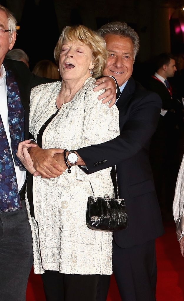 """The Dowager Countess making this face while getting hugged by Dustin Hoffman:   29 Photos Of The Cast Of """"Downton Abbey"""" Being Totally Un-Downton-Like"""