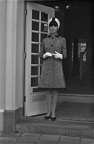 Holthaus-herst-wintercollectie-look (1965)             Een model uit de nieuwe herfst-wintercollectie van de amsterdamse couturier dick holthaus: sophia toont hier een tweedmantel in zwart en wit met opgestikte panneaux en grosgraingarnering. Een wit vilten helmhoed completeert het geheel.