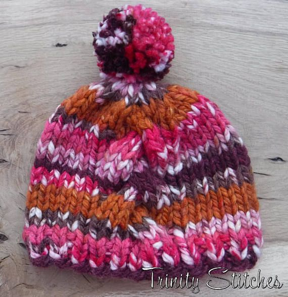 Hand knit pom pom and cable knit hat. Made with super bulky weight 85% Acrylic, 15% Wool yarn. Colorway: Gramercy Park  Measures 18 in circumference and 8 in height, unstretched (exclusive of pom pom).  Fits teen/adult female head.  Care: Hand wash cold, preferably with a wool wash.