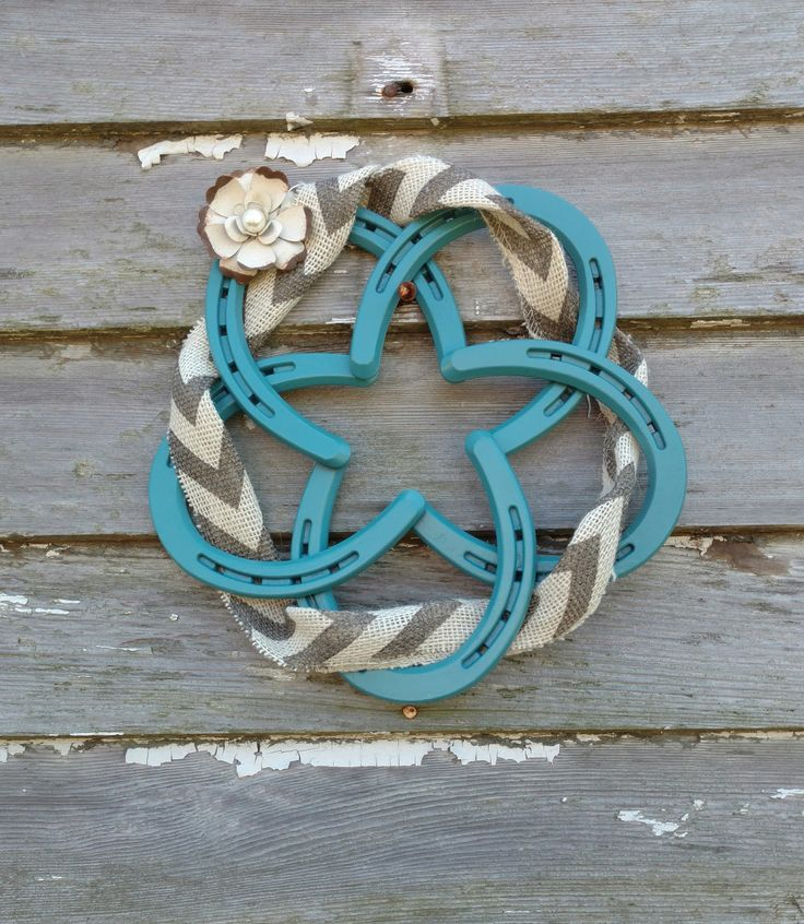 Light blue horseshoe wreath. Decorated with metal flower and burlap. We can also do different colors if ordered with a custom order.