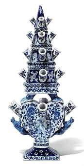 A DUTCH DELFT-STYLE BLUE AND WHITE TULIPIERE LATE 19TH/20TH CENTURY, BLUE VE/2/4 MARK Surmounted by a rectangular section obelisk issuing spouts supported on lion's paw feet above a heart-shaped vase issuing further spouts with leopard handles, on a spreading rectangular base painted with Cupid and flowers 18 in. (25.8 cm.) high