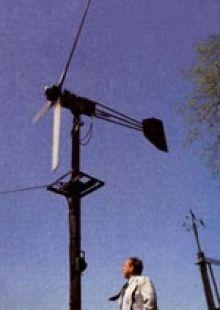 Homemade windmill generator constructed from an ambulance alternator, a surplus automotive drivetrain, redwood blades, and batteries.