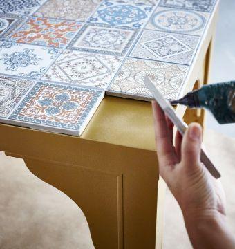 Dessus d'une table IKEA LACK peinte en dor en train d'tre recouvert de carreaux dcoratifs.   #epinglercpartager