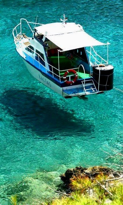 Crystal Waters in Halkidiki, Greece - it looks like the boat is floating on the air, not the sea