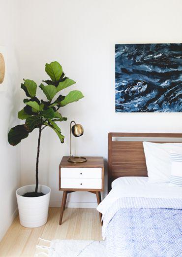 fiddle leaf fig, bedside table, wooden headboard, mid-century design, art over bed