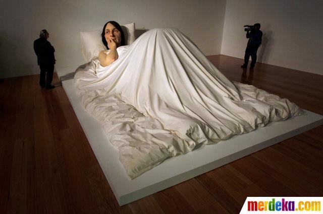"""Wartawan berdiri di samping patung wanita berjudul """"In Bed"""" yang dibuat oleh pematung Australia Ron Mueck saat pameran di Museum Seni Kontemporer (MARCO) di Monterrey, Meksiko."""
