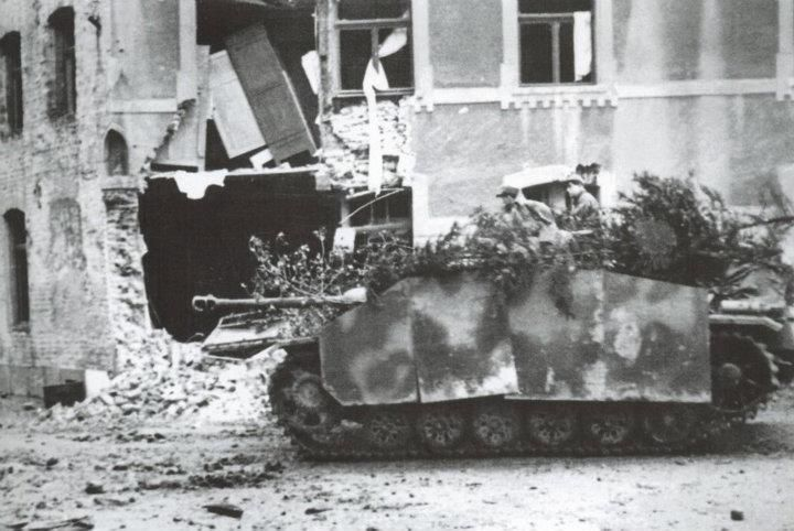 StuG III Ausf G passing through a town during the battle of the Bulge.