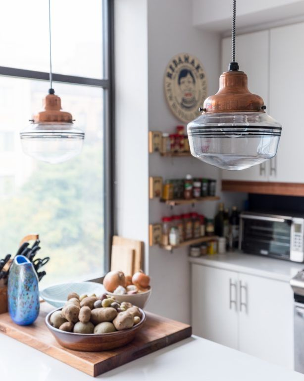 Elegant copper schoolhouse lighting in a fashionable New York apartment's kitchen.