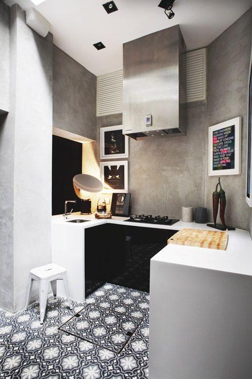 Joli jeu de matières et de couleurs ; carrelage graphique au sol, meubles noirs et plan de travail blanc, béton ciré aux murs | modern kitchen, printed tiles, concrete wall