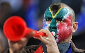 A man blowing a vuvuzela – this is common at South African sporting events
