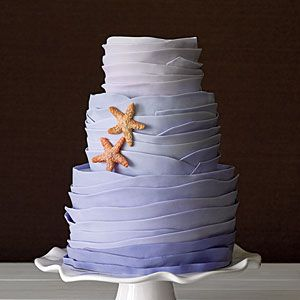 Coastal Wedding Cakes | High Tide: Triple lemon—lemon pound cake, lemon curd, and lemon buttercream filling—with ombre blue rolled-fondant waves and sugar starfish.