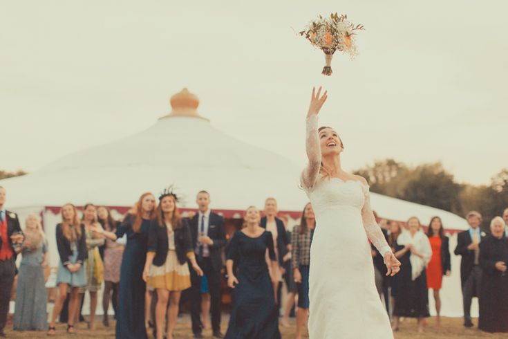 Bride throwing bouquet with LPM Bohemia Grand Pavilion in the background