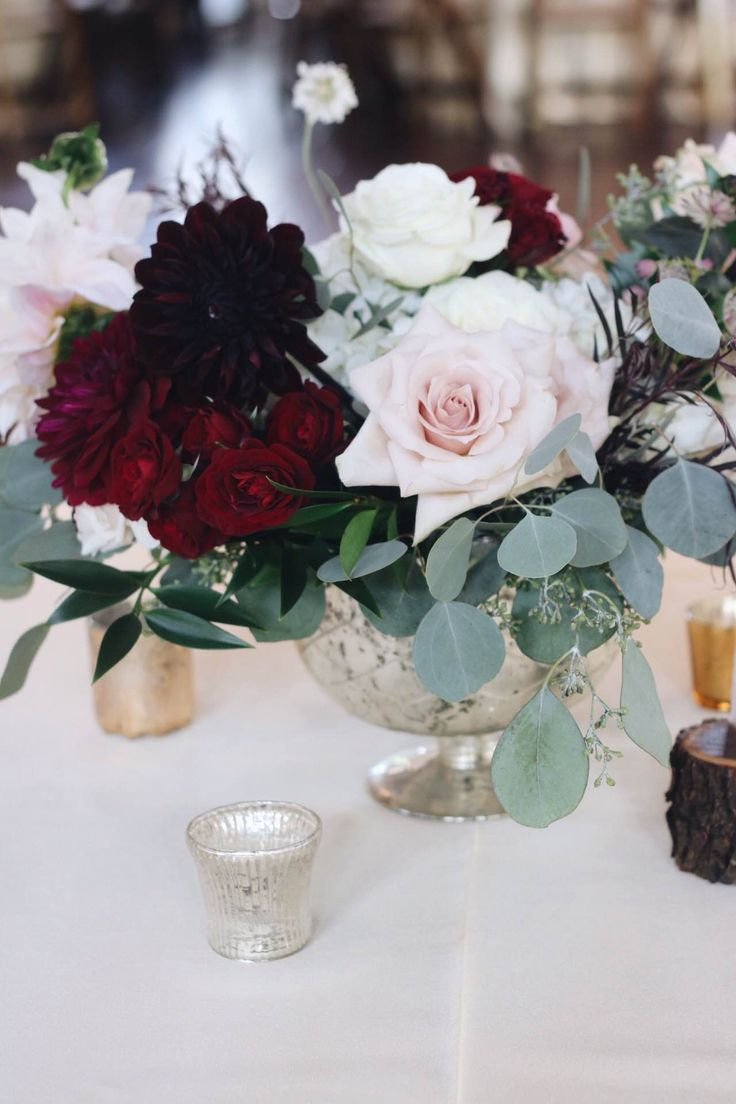 Blush and burgundy flowers in a loose, textured arrangement. | Whim Florals