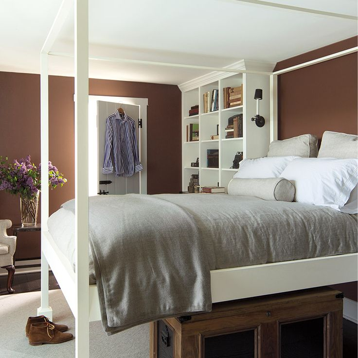 Bedroom with brown walls and elevated four poster bed.
