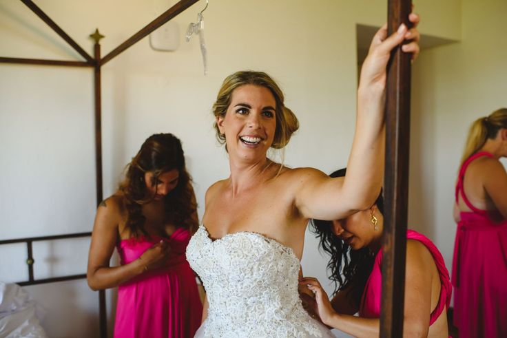 Bride is getting dressed with Private Lable by G wedding dress, Bridesmaids in pink gowns helping. Cake & Confetti Weddings. Photo by Quemcasaquerfotos