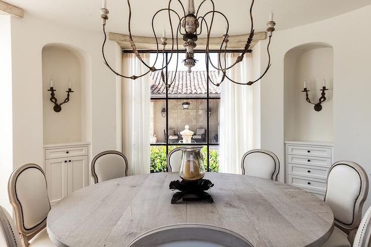 A round Mediterranean dining room features a French candle chandelier illuminating a round reclaimed wood dining table lined with cream French dining chairs with brass nailhead trim.