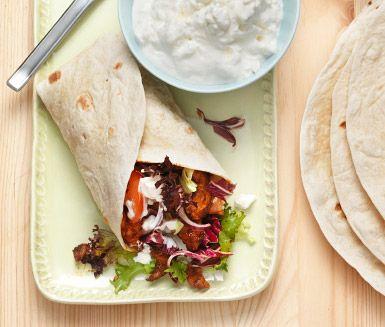 Recept på kryddiga kycklingwraps med utsökt fetacrème. Du marinerar kyckling i olja med chilipulver och vitlöksklyftor och serverar i tortillabröd  tillsammans med tomat, rödlök, sallad och kräm av gräddfil och fetaost.