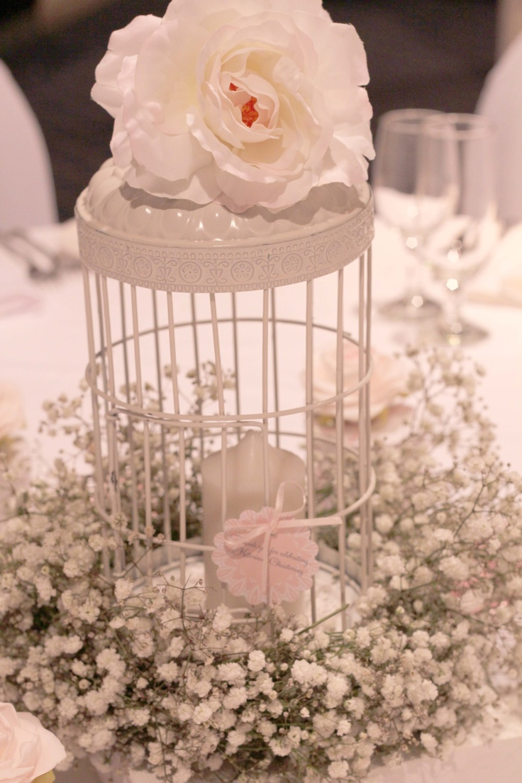 Birdcage centrepieces adorned with silk flower and baby's breath wreath