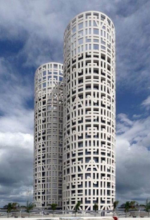 "The Spanish architectural firm of Rafael de La-Hoz, have completed the Torres de Hercules. The two cylindrical white towers are located in the Bay of Algeciras in Southern Spain. Two cylindrical, white towers rising from a flat pool of water. On the façade-a giant lattice-appears the mythical motto from the legend of the Pillars of Hercules, ""Non Plus Ultra"" (nothing further beyond), warning sailors in the Mediterranean of the edge of the known world."
