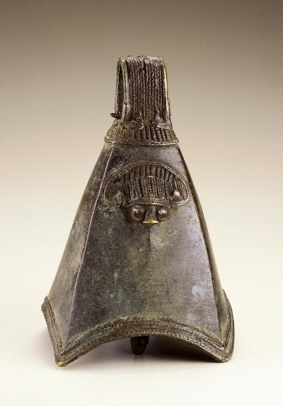 Africa | Yoruba bell. Nigeria | Early 20th century | Copper alloy | Most four-sided bells are associated with the Benin kingdom, where they are placed on ancestral altars and were once worn by the king's soldiers. The curved opening, sharply tapered sides and stylized face suggest that this bell is instead from the neighboring Yoruba peoples.